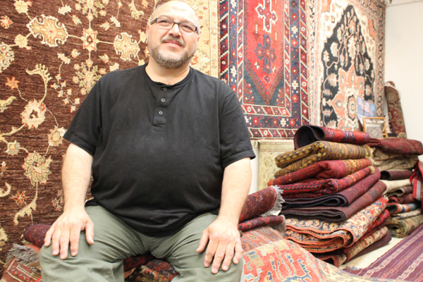 Gencer Gokeri, the owner of Fremont's Istanbul Imports, sits on a stack of handmade, tribal rugs that he brought over from Turkey. (Photo by Allison Int-Hout)