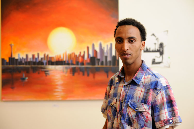 "Abraham Tesfelaise, with his painting ""Seattle"" at the Downtown YMCA. (Photo by Coleen McDevitt)"