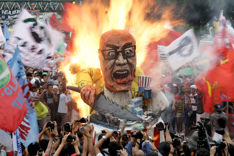 Protesters burn an effigy of Philippine President Benigno Aquino III during a rally to coincide with his fourth State-of-the-Nation Address (SONA) on Monday July 22. (Photo by Bullit Marquez / AP)
