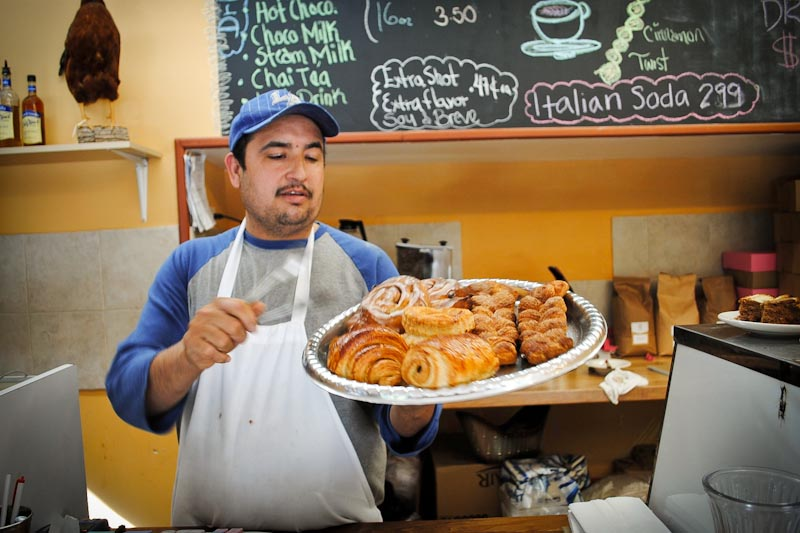 Angel Rocha shows off a diverse sampling of baked goods prepared at Golden Wheat, in the Central District. (Photo by Anna Goren)