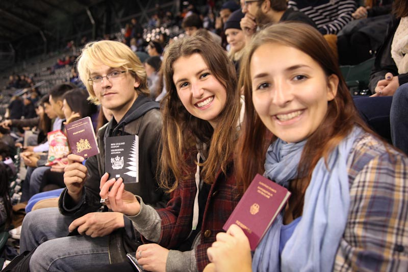 University of Washington international students (from left) Hans Mohrmann from The Netherlands, Tess Murphy of New Zealand and Anna WüŸst of Germany show off their passports at a Mariners to celebrate the first day of class. (Photo by Alex Stonehill)