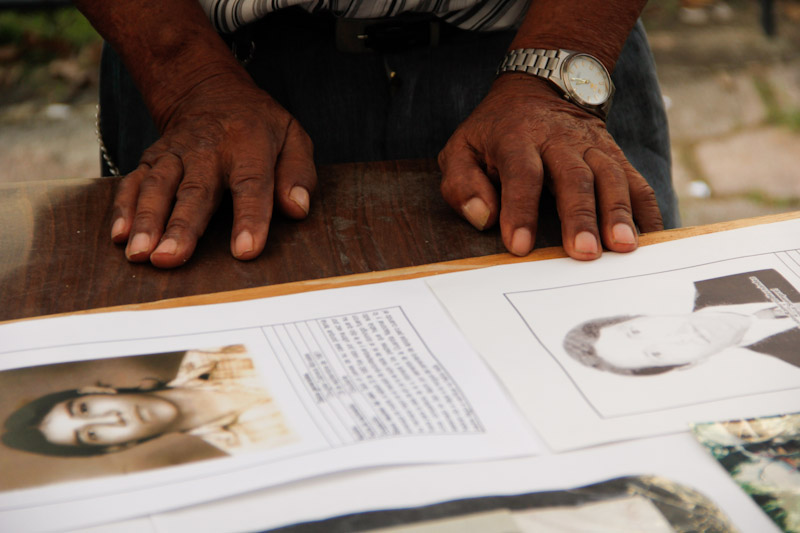 "An elder Salvadoran man who survived the armed conflict is preparing a poster memorializing slain family members for the annual ""Encuentro de Victimas"" (Meeting of Victims) in San Salvador, El Salvador. (Photo by Alex Montalvo)"