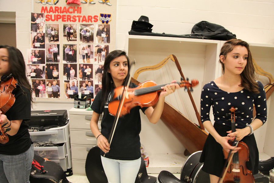 Mailarie Muñoz, age 16 (center) and Jennifer Bravo, age 16 (right), during the intermediate Mariachi class program at Wenatchee High School. (Photo by Alex Stonehill)