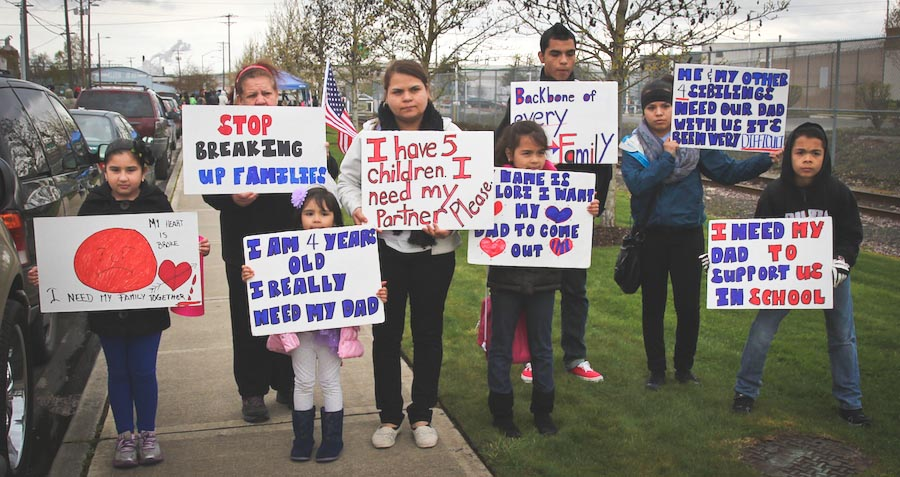 The family of detainee hold signs outside Northwest Detention Center during a demonstration on Saturday. (Photo by Lael Henterly)
