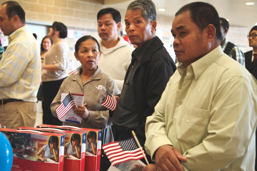In line at a citizenship swearing in ceremony in Tacoma. Immigrants and new citizens are disproportionately targeted by criminals and scammers, advocates say. (Photo by Alex Stonehill)