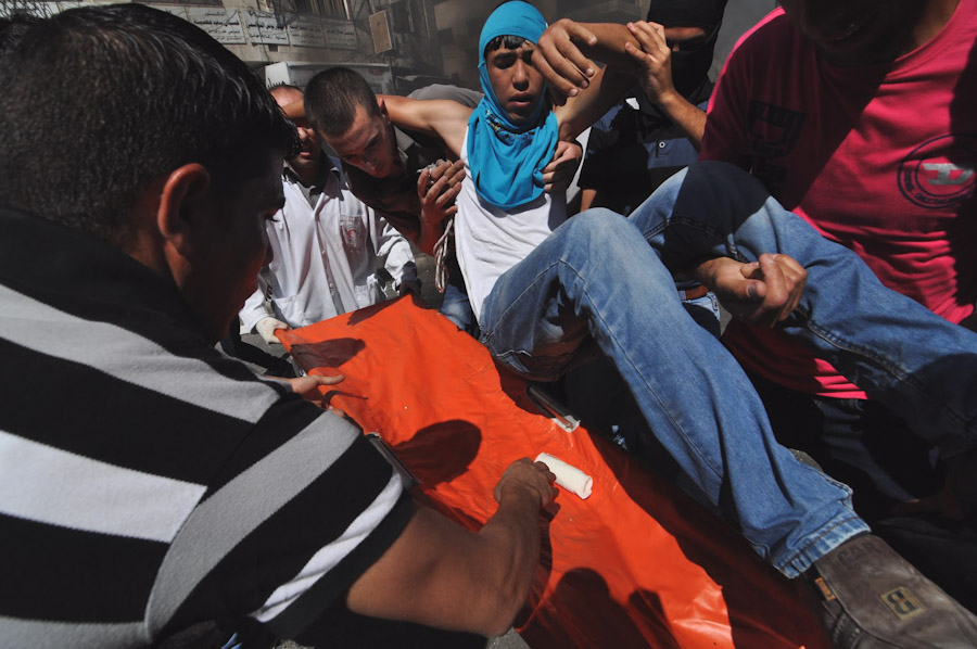 Protesters carry a wounded teenager to a waiting stretcher after a protest in Hebron devolved into clashes between stone throwers and Israeli soldiers. (Photo by Tom James)