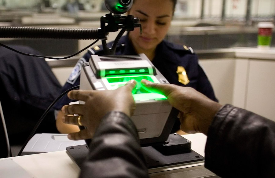 An international visitor arriving at Washington Dulles Airport is fingerprinted as part of a system to track undocumented immigrants and prevent visa overstays. (Photo by Dept. of Homeland Security)