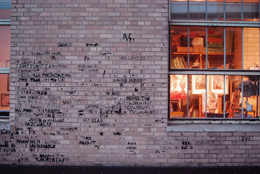 Detainees left their marks on the walls of the building's outdoor recreation courtyard using melted roofing tar. Many left their names and from where they emigrated. (Photo by Ana Sofia Knauf)