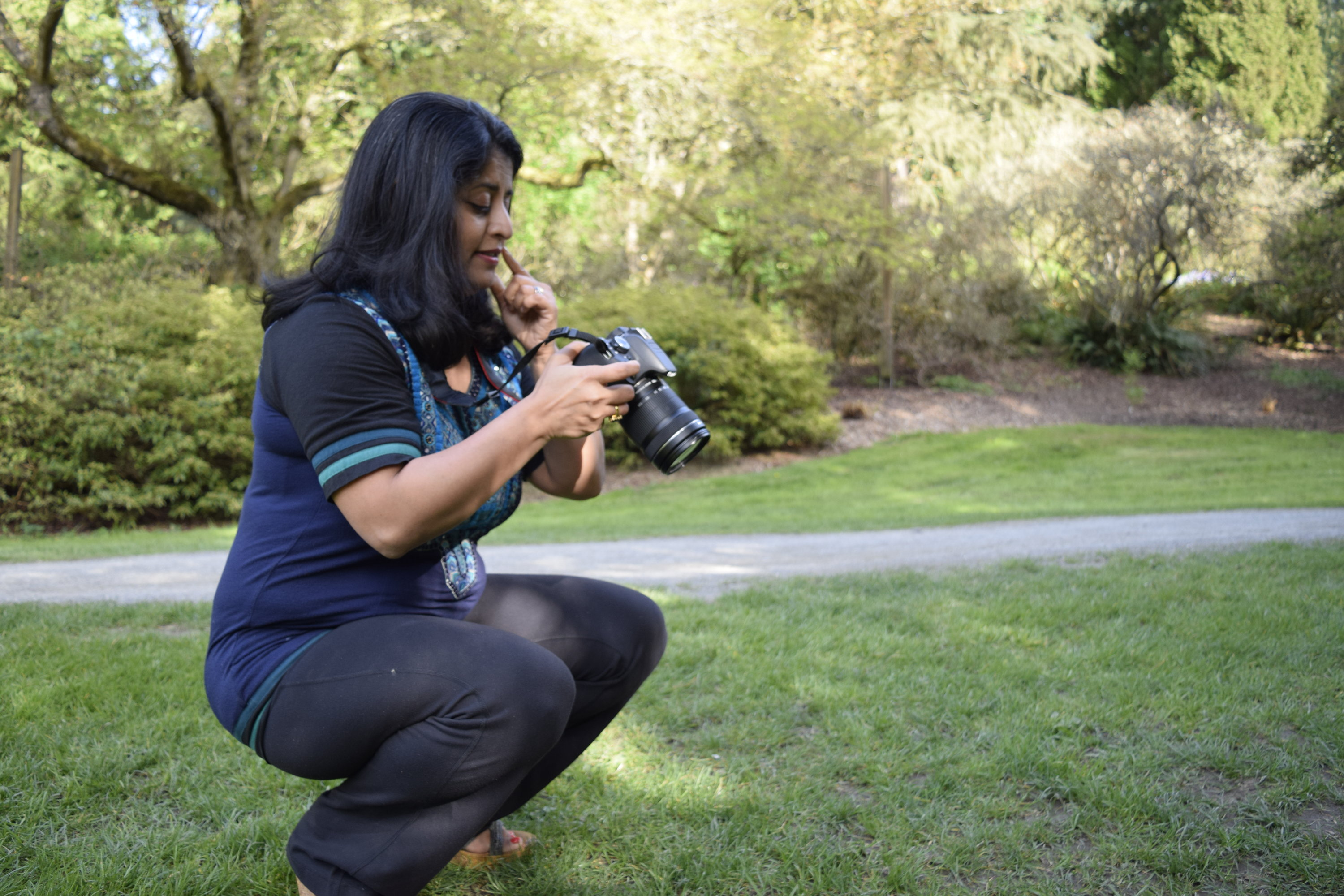 Sudeshna Sen looks at photos she has taken in the Arboretum in Seattle, Wash. for site development on a future video project. (Photo by Rayna Stackhouse)
