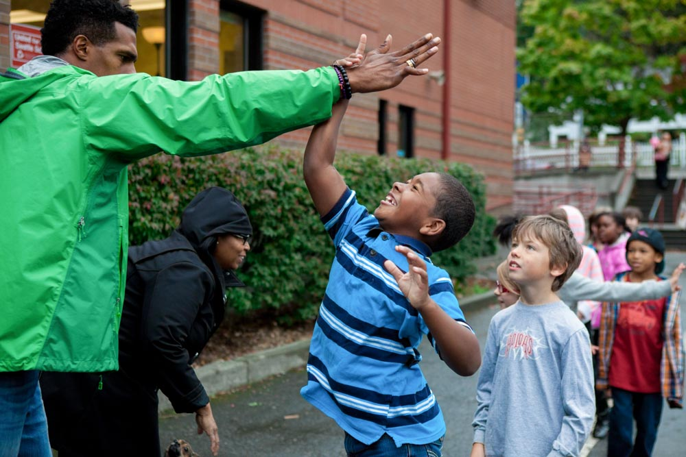 Gabriel Ray Pierre (left) high fives a student at Leschi Elementary School on Friday, as part of #SeattleHigh5. The event aimed to show children of color positive images of black men and women in their community. (Photo by Jovelle Tamayo)