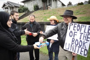 Zainab Haji (left) gives cookies to Kent Chadwick, who turned out in support of the Islamic Center of Kitsap County in 2015 in response to announced plans for an anti-Islam rally the Bremerton mosque. No protestors actually showed up. (Photo courtesy CAIR-WA)