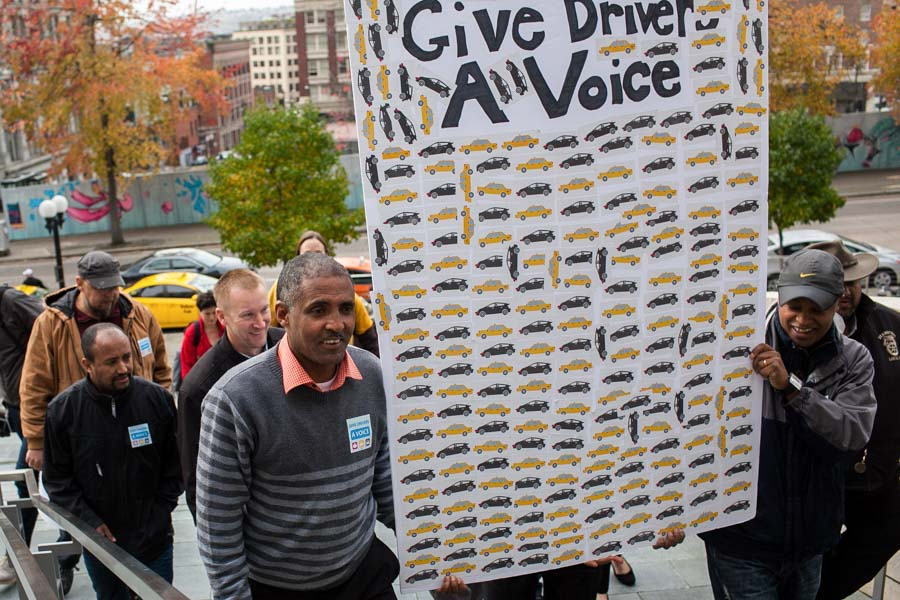 Taxi drivers Getachew Mersha (left) and Dawit Tesfaye lead a group of drivers and community members on their way to deliver a petition to Mayor Ed Murray's Office requesting rideshare drivers be allowed to unionize. (Photo by Jovelle Tamayo)