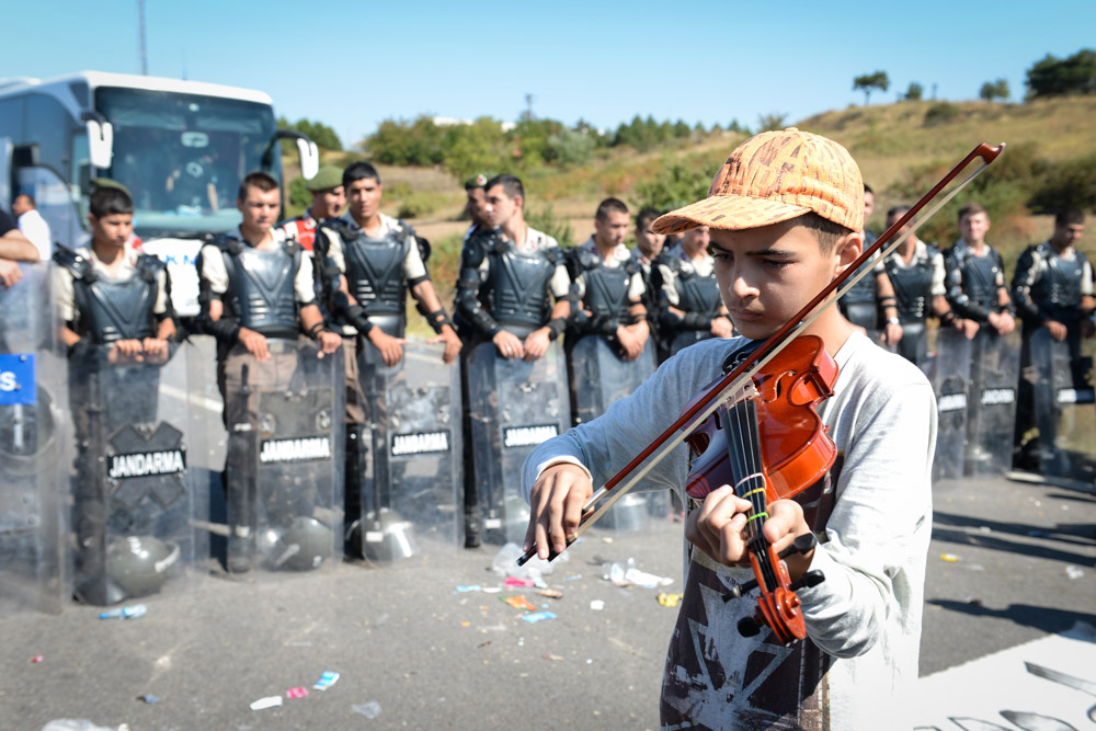 A young refugee plays violin in front of a line of Turkish police at Edirne, where refugees amassed hoping to cross into Bulgaria. (Photo by Levent ......)