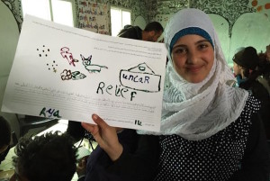 """A Syrian girl holds up a poster she drew """"about how she recently helped someone using information or technology"""" during UW professor Karen Fisher's workshop at Za'atari refugee camp in Jordan in January 2015. (Photo courtesy of Karen Fisher, University of Washington Information School)"""