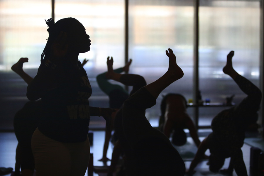 Irene Auma, at center, helps conduct a yoga class at Thursdayin Seattle. Auma plans to start the first yoga-in-prisons program in Kenya. (Photo by Ken Lambert / The Seattle Times)