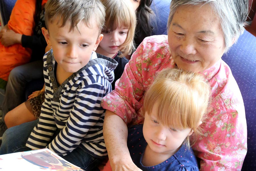 "Fen Fang Jiang, 72, reads to kids at Pike Market Childcare in the Pike Place Market. Jiang is part of the ""Foster Grandparent"" program. (Photo by Greg Gilbert / The Seattle Times)"