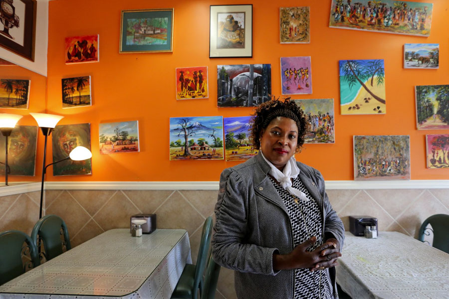 Jane Kagira owns the Kenyan restaurant Safari Njema in Columbia City, host of the first Migrating Meals conversation. The scenes on the wall mainly are depictions of Kenya. (Photo by Alan Berner / The Seattle Times)