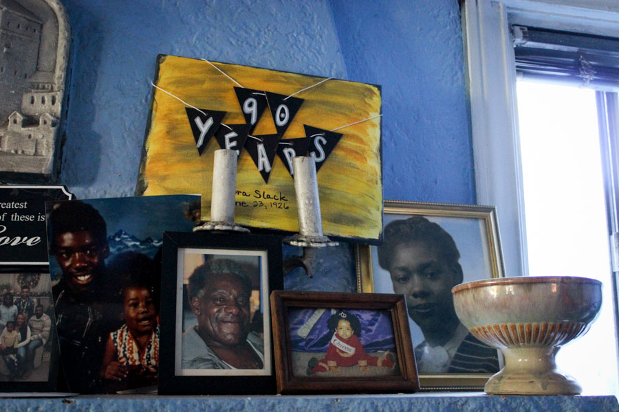 Photos of the Slack family on the mantle of their Central District home, including little painting made for Dora Slack's 90th birthday in June. (Photo by Alia Marsha)