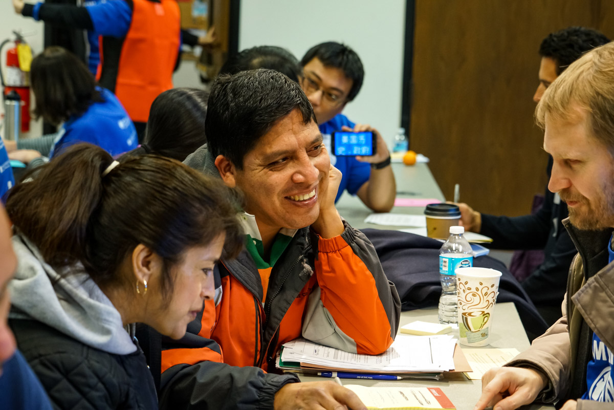 A family talks with a volunteer about any potential red flags regarding their citizenship application at a 2016 citizenship workshop held by the Seattle Office of Immigrant and Refugee Affairs. (Photo by Alabastro Photography)