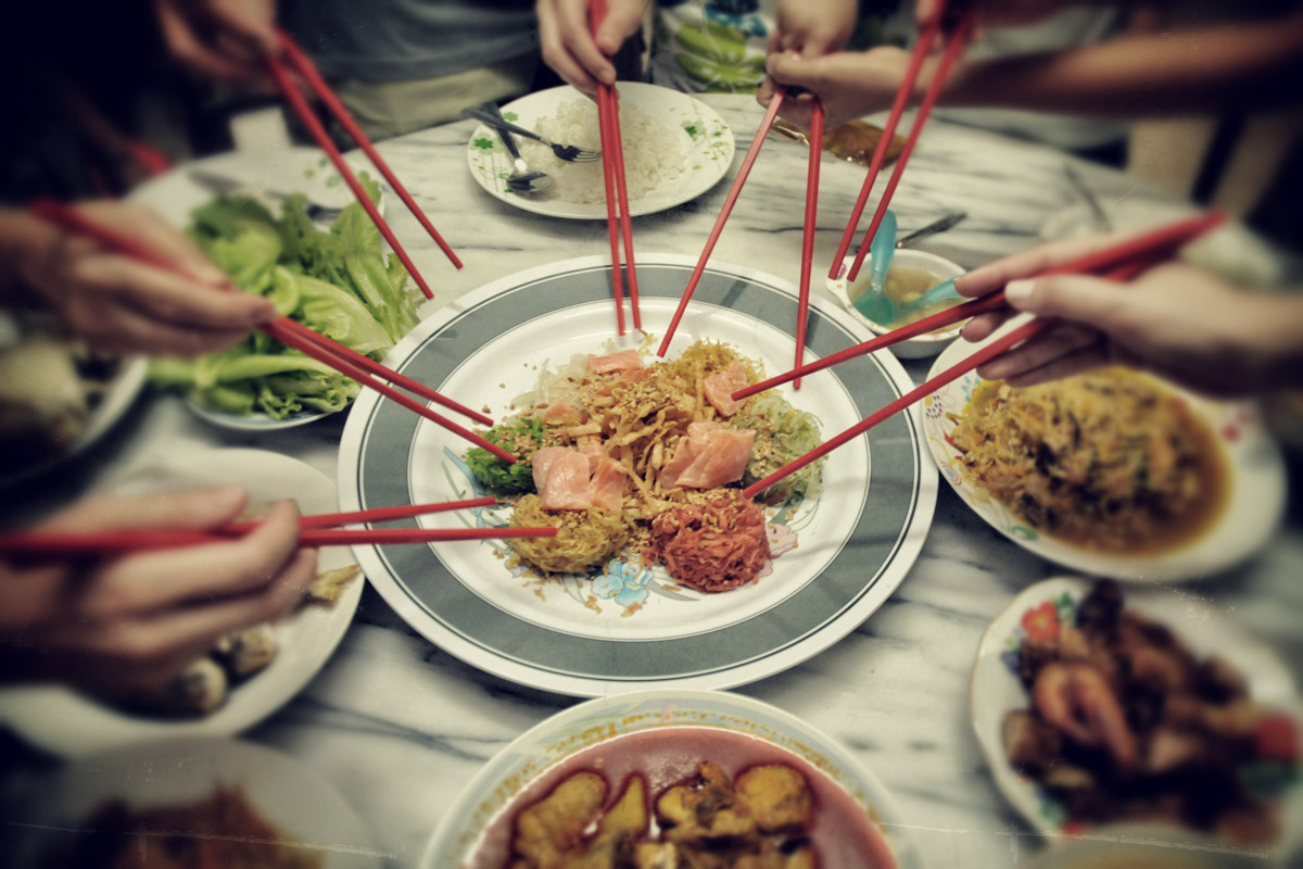 Getting ready to toss yee sang aka yu sheng. (Photo from Flickr by C.K. Koay)