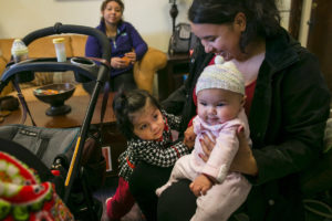 Martha Langarica, right, holds her 4-month-old daughter, Mia, as Evelyn Reyes, 16 months old, takes a closer look. The families were visiting Open Arms Perinatal Services to get advice from the doulas and personnel at the center, as well as diapers. (Photo by Johnny Andrews / The Seattle Times)